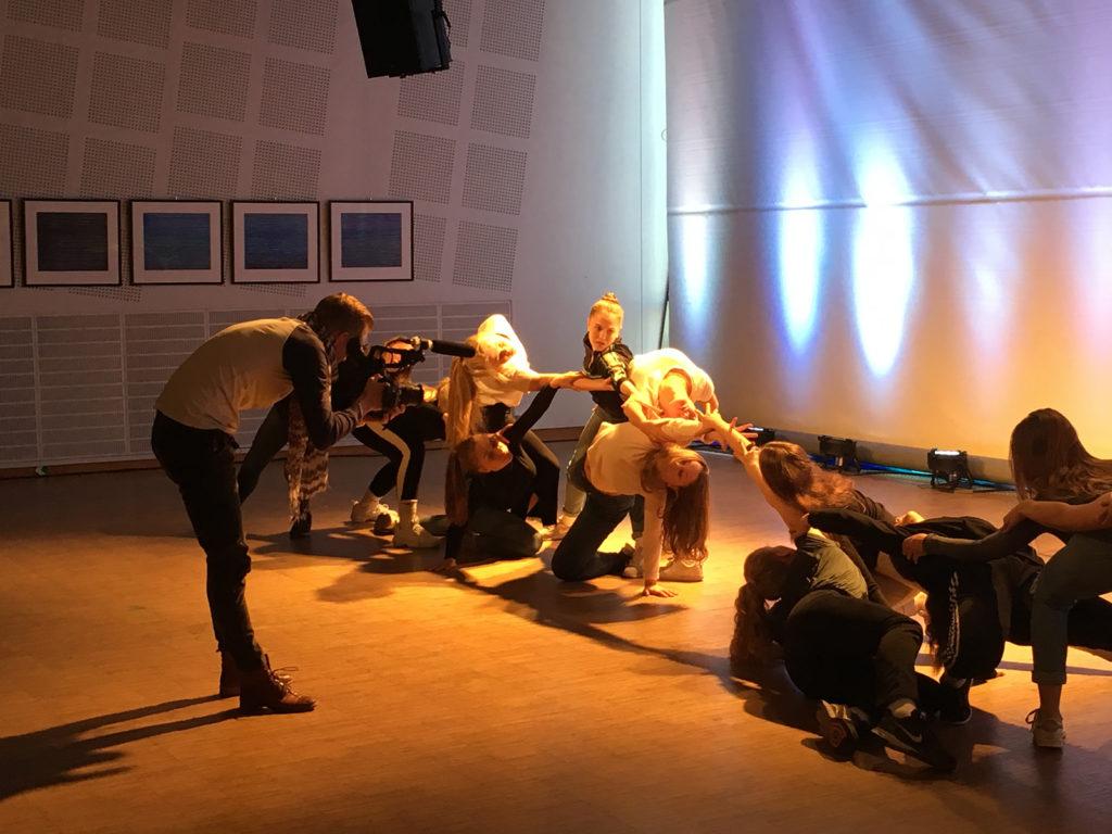 En man filmer elevene som danser.